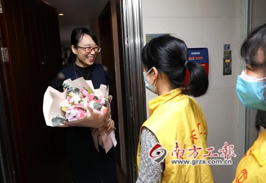 援鄂医生谢东平的妻子一大早就收到工会志愿者送上的鲜花,笑得很开心 林景余摄.JPG